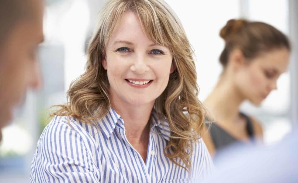 Affärskvinna som ser glad ut - Teamout erbjuder kvalificerade ledarskapsutbildningar inom UGL, utveckling av grupp och ledare